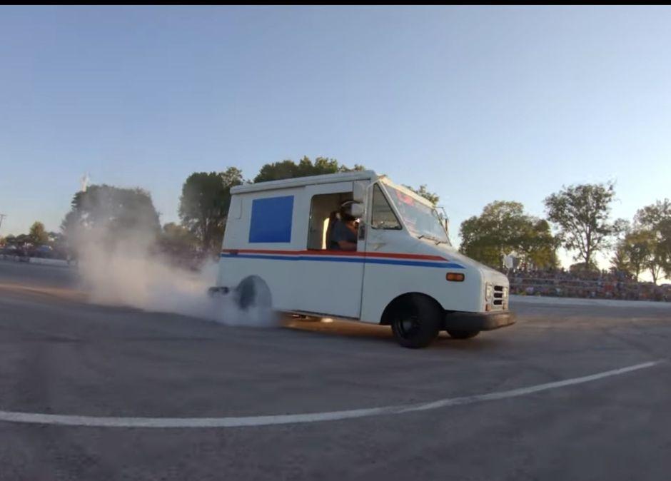 Mira a un camion del correo de los Estados Unidos hacer donas en el pavimento
