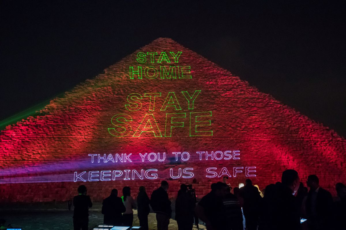 """La Gran Pirámide de Keops en El Cairo, muestra un letrero que dice """"Quédate en casa, mantente a salvo. Gracias a quienes nos mantienen a salvo""""."""