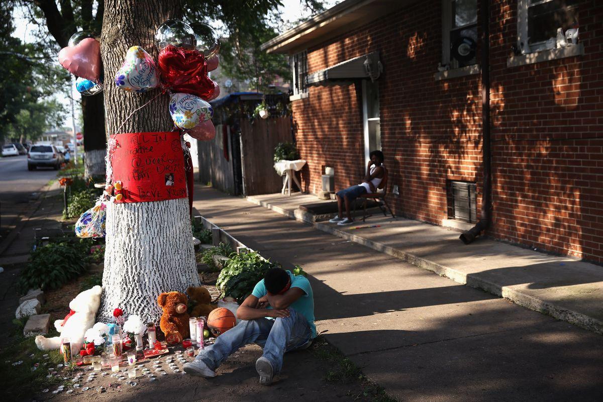 Un joven se duele junto a la ofrenda a una víctima de la violencia con armas de fuego en Chicago.
