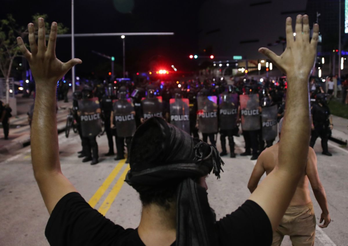Manifestante frente a la policía en una protesta en Miami.