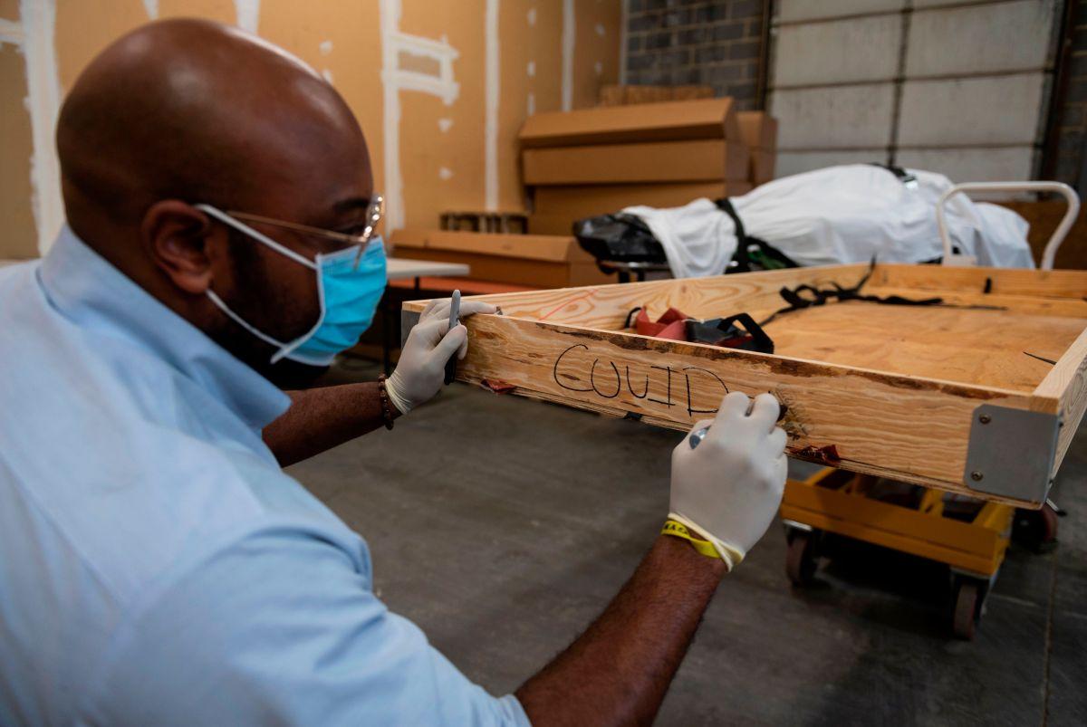 Transportista funerario escribe en el costado de una caja antes de depositar los restos de una víctima de Covid-19.
