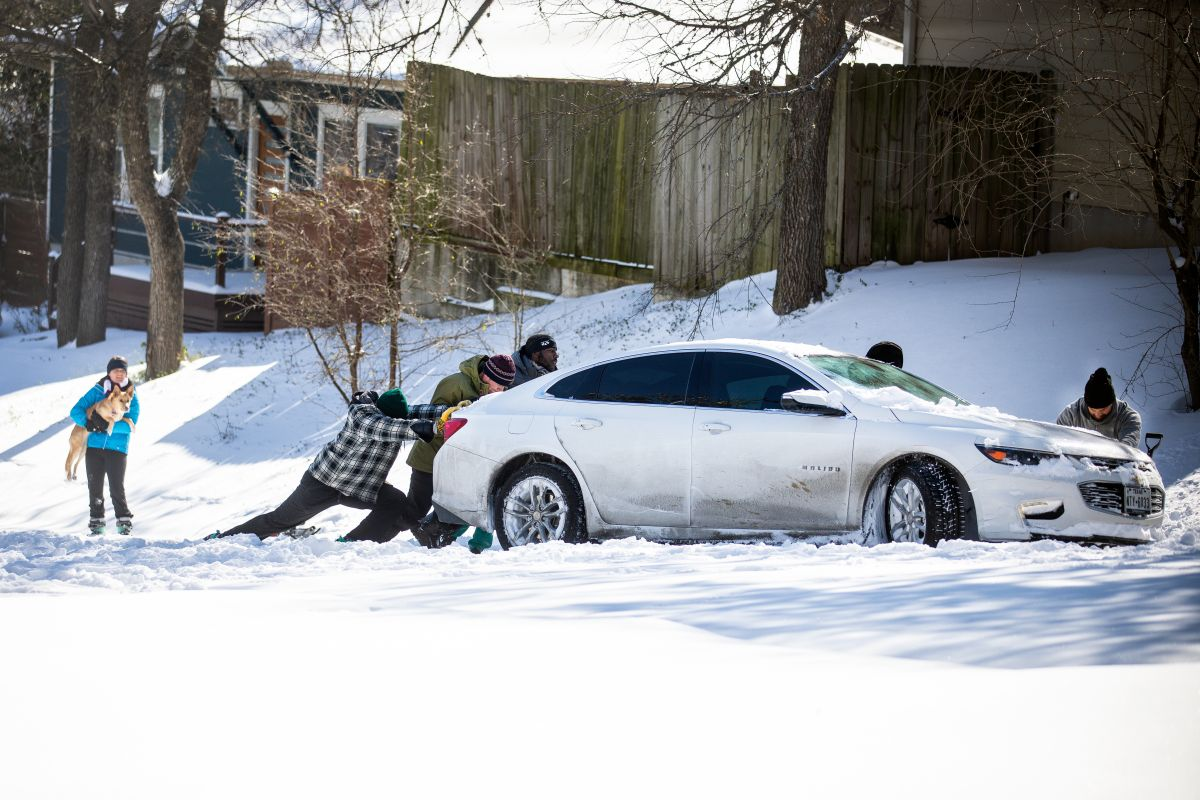 Residentes del este de Austin empujan un automóvil fuera de la nieve el 15 de febrero de 2021 en Austin, Texas.