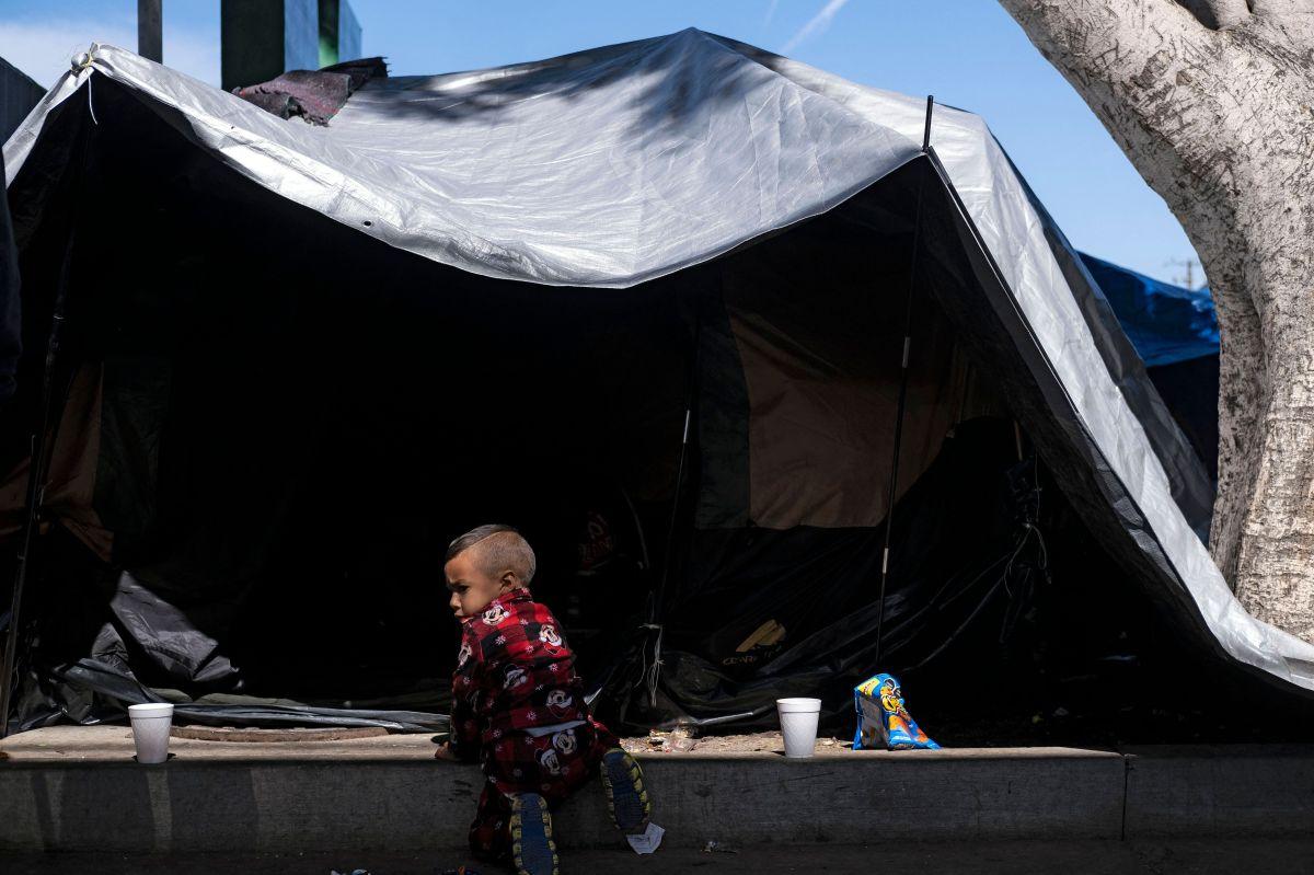 Niño migrante juega cerca de una carpa en un campamento de migrantes en la frontera de México y EE.UU.