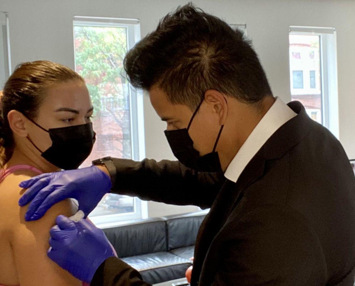 Juan Aguirre, enfermero del Centro Médico Alivio, vacuna contra el coronavirus a Kimberly Ferral en su casa en el barrio de Pilsen. (Cortesía Centro Médico Alivio)