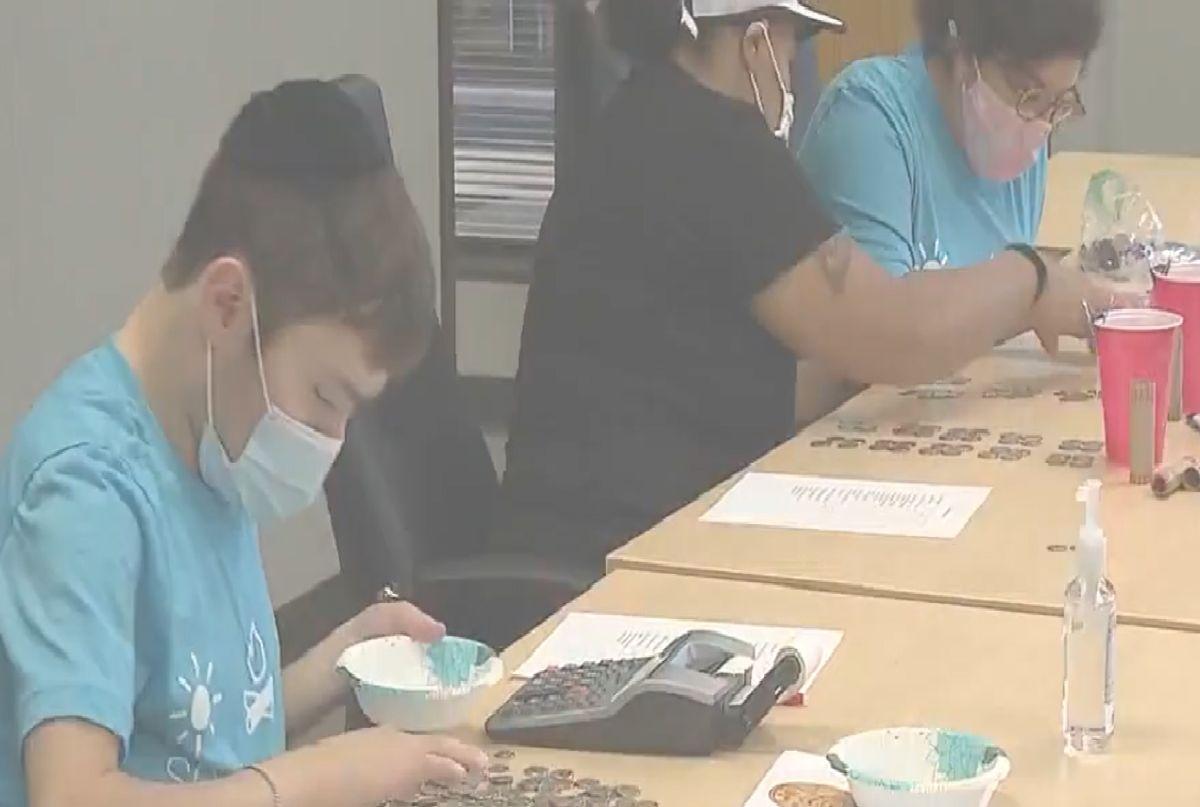 Adultos con discapacidad separan, enrollan y cuentan monedas a través del programa  'Coins for Keshet'. Foto captura Fox 32 Chicago